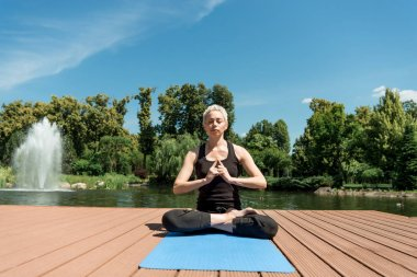 athletic woman practicing yoga in lotus pose on yoga mat near river in park
