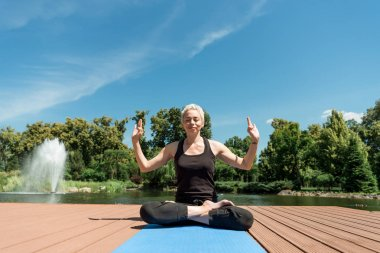 happy woman practicing yoga in lotus pose on yoga mat near river in park
