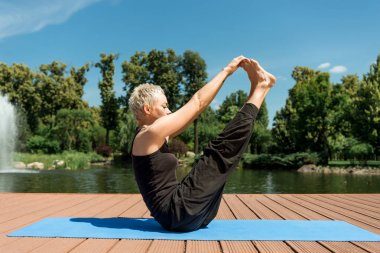 side view of woman practicing yoga and stretching legs on yoga mat near river in park