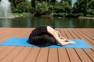 side view of woman practicing yoga in Wide Child pose (Balasana) on yoga mat near river in park