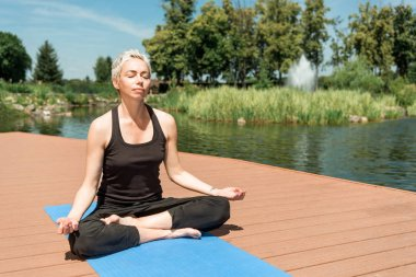 woman practicing yoga in lotus pose and meditating on yoga mat near river in park
