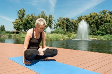 sporty woman practicing yoga in lotus pose on yoga mat near river in park