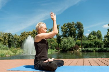 side view of woman practicing yoga in lotus pose and hands in namaste gesture on yoga mat near river in park