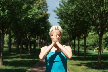 woman practicing yoga and standing with hands in namaste gesture in park