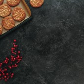 Fotografie top view of freshly baked cookies on tray and red berries on black concrete surface