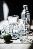 Fotografia vista ravvicinata della calce fresca e bicchieri vuoti con messa a fuoco selettiva, shaker