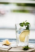 Photo close-up view of glass with fresh cold summer drink and ice cubes