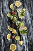 Fotografie top view of fresh cold summer cocktails in glasses on wooden table