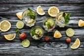 Draufsicht auf kalte Sommercocktails in Gläsern und Zutaten auf Holztisch