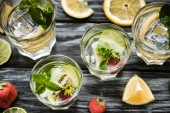 Fotografie Draufsicht der Gläser mit leckeren Erdbeer-Kiwi Mojito cocktail auf Holztisch