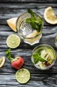 Fotografie Nahaufnahme von Gläsern mit leckeren Erdbeer-Kiwi Mojito cocktail auf Holztisch