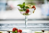 close-up view of delicious summer cocktail with mint, lime, lemon and strawberries in glass