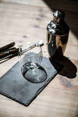 close-up view of shiny empty glass on slate board, shaker and tongs on wooden table
