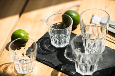 close-up view of empty glasses, tongs and fresh limes on wooden table