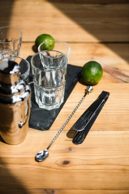 high angle view of empty glasses, shaker, tongs and fresh limes on wooden table