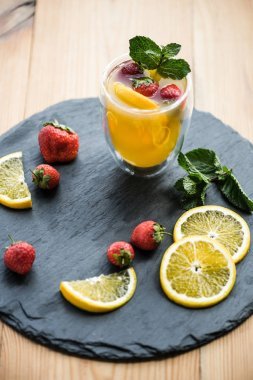 high angle view of fresh delicious summer drink with mint and fruits on slate board