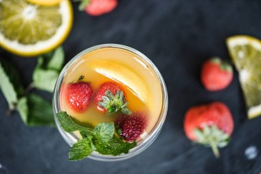 top view of fresh refreshing summer drink with mint and fruits on slate board