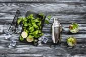 Fotografia vista superiore di menta fresca, pinze, shaker e kiwi fragola mojito in vetri