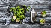 Draufsicht auf frische Minze, Zange, Shaker und Erdbeer-Kiwi-Mojito in Gläsern auf Holztisch