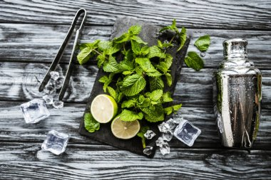 top view of ingredients for making mojito, tongs and shaker on wooden surface