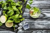 Glasoberseite mit frischer kalter Erdbeere und Kiwi-Mojito auf Holztisch