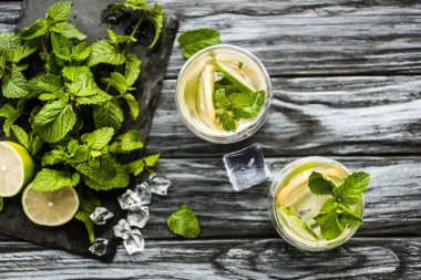 top view of glasses with mojito and fresh ingredients on wooden surface