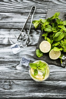 top view of ingredients for making mojito and glass on wooden surface