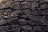 Detailní pohled staré zvětralé hrubé šedé zdi texturou pozadí