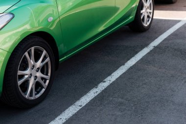 detail of green shiny car on parking lot