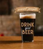 Fotografie Detailní pohled skla s lahodné tmavé pivo na stole v hospodě s inspirací chytré lidi pít dobré pivo