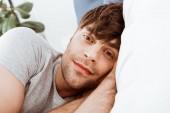 Detailní záběr portrét člověka při pohledu na fotoaparát a ležím v posteli doma