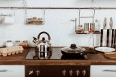 Fotografie selective focus of modern kitchen interior with frying pan and teapot on stove