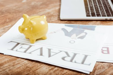 close up view of piggy bank on travel newspaper at table with laptop