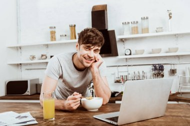 happy young male freelancer eating corn flakes on breakfast at table with laptop in kitchen at home