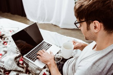 side view of male freelancer with coffee cup working on laptop with blank screen in bed at home