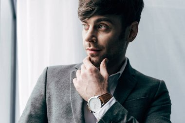 portrait of thoughtful young businessman with watch looking away