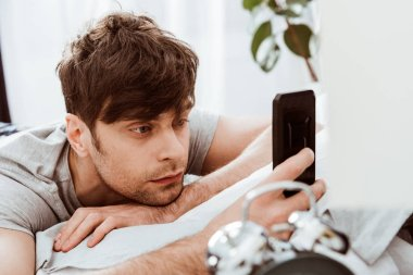 selective focus of man using smartphone while laying in bed at home