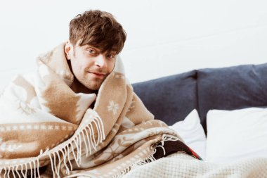 cheerful sick young man wrapped in blanket sitting on bed at home