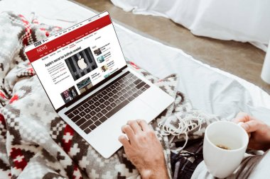 cropped image of man holding coffee cup and using laptop with bbc news on screen in bed at home