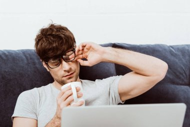tired male freelancer in eyeglasses holding coffee cup and sitting on bed with laptop at home