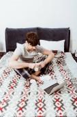 Fotografie mladý muž freelancer s šálek kávy sedí na posteli s notebookem doma