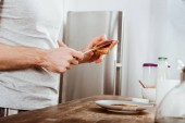 Photo partial view of man spreading toast by jam in kitchen at home