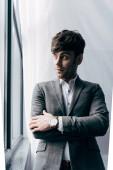 Fotografia giovani uomo daffari Pensive in giacca che osserva via in ufficio