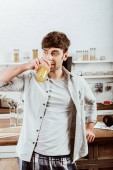 Fotografie man drinking orange juice on breakfast in kitchen at home