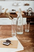 Fotografie close up view of remote car key, bottle of water and branch in vase at wooden table in kitchen