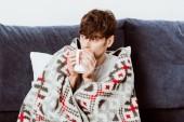 Fotografie Selektiver Fokus eines Kranken, der zu Hause in eine Decke gehüllt Tee trinkt