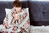 erhöhte Ansicht des kranken Menschen in Decke sitzend mit Tasse Tee im Bett zu Hause gewickelt