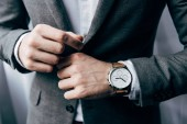 partial view of businessman with watch buttoning up jacket