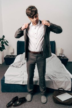 businessman putting on jacket in bedroom at home