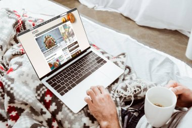 cropped image of man holding coffee cup and using laptop with bbc food on screen in bed at home
